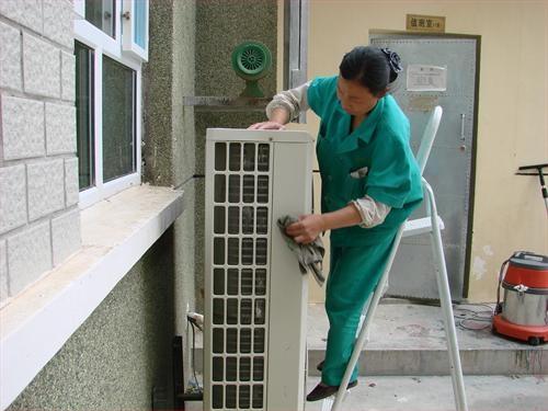 维修人员在清洗空调。资料图片